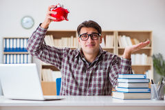 The student breaking piggybank to pay for tuition fees Royalty Free Stock Photo