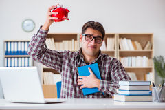 The student breaking piggybank to pay for tuition fees Royalty Free Stock Photography