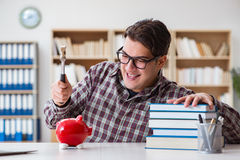 The student breaking piggybank to pay for tuition fees Royalty Free Stock Image