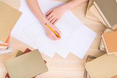 Student is busy writing at the desk Royalty Free Stock Photography
