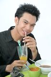 Student at cafeteria. Student having meal at canteen or cafeteria and drinking orange juice with straw Stock Photo