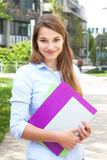 Student on campus smiling at camera Royalty Free Stock Photo