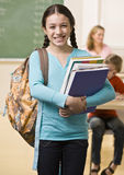 Student carrying backpack and books Stock Images