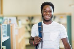 Student Carrying Backpack In Library Stock Images