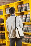 Student Carrying Bag While Standing In College. Rear view of male student carrying bag while standing against bookshelves in college library Royalty Free Stock Photography