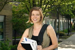 Student Carrying Books on Campus. A female student holding books while walking around campus Royalty Free Stock Image