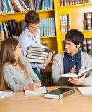 Student Carrying Books While Friends Sitting In Royalty Free Stock Image