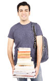 Student carrying books. Young student carrying a heavy stack of books Royalty Free Stock Photo