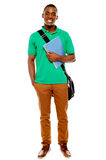 Student carrying laptop bag and notebook. Smiling african student carrying laptop bag and notebook, full length portrait Royalty Free Stock Photography