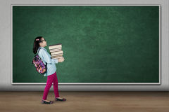 Student carrying pile of books in classroom Stock Images