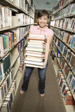 Student Carrying Stack Of Books In The Library Royalty Free Stock Photography