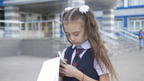 Student-centered elementary school in school uniform writes or draws something in a notebook near the school building.