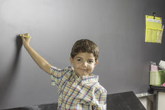 Student Chalk Board. A young male student writing on the chalkboard in a classroom Royalty Free Stock Photos