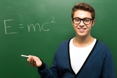 Student by chalkboard with e=mc2 Stock Photography