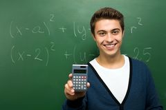 Student by chalkboard holding calculator Stock Photography