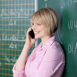 Student chatting on her mobile in the classroom Royalty Free Stock Photos