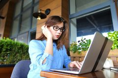 Student chatting by laptop with friends at cafe. Female student chatting with friends by laptop at cafe. Young girl dressed in jeans shirt sitting near window royalty free stock image