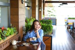 Student chatting by laptop with friends at cafe. Female student chatting with friends by laptop at cafe. Young girl dressed in jeans shirt sitting near window royalty free stock photo