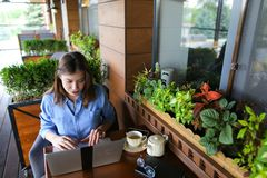 Student chatting by laptop with friends at cafe. Female student chatting with friends by laptop at cafe. Young girl dressed in jeans shirt sitting near window stock photos