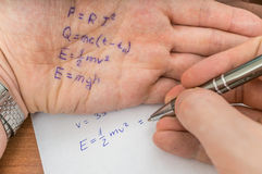 Student is cheating during exam with cheat sheet with formula. Written on his hand royalty free stock photography