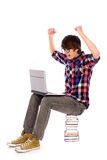 Student cheering with laptop. Young man sitting on pile of books Stock Image