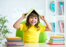 Student child with a book over her head Stock Images