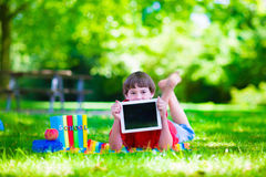 Student child with tablet computer in school yard. Child in school with tablet pc. Smart teenager student boy studying and learning outdoors, reading books Royalty Free Stock Image