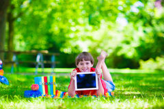 Student child with tablet computer in school yard. Child in school with tablet pc. Smart teenager student boy studying and learning outdoors, reading books Stock Photos