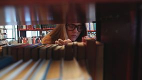 Student chooses a book in the library. Girl Student chooses a book in the library, close up stock video