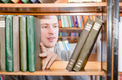 Student chooses a book on a shelf in the library Royalty Free Stock Photos
