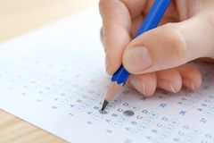 Student choosing answers in test form to pass exam. At table royalty free stock photo
