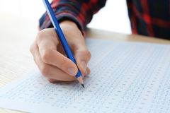 Student choosing answers in test form to pass exam. At table royalty free stock image