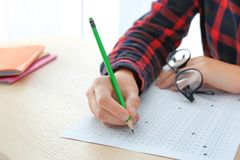 Student choosing answers in test form to pass exam. At table stock photography