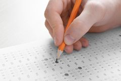 Student choosing answers in test form to pass exam. At table royalty free stock photos
