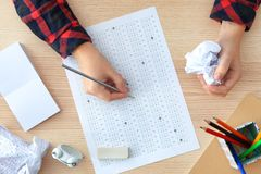 Student choosing answers in test form to pass exam. At table royalty free stock images