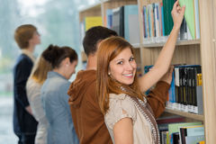 Student choosing book from bookshelf in library. Student choosing book from bookshelf with friend in college library Stock Photo