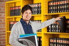 Student Choosing Book From Shelf In Library. Portrait of happy male student choosing book from shelf in college library Royalty Free Stock Image