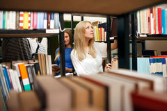 Student choosing books. In university library Royalty Free Stock Image