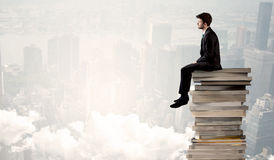 Student in city sitting on stack of books Stock Photos