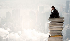 Student in city sitting on stack of books Royalty Free Stock Image