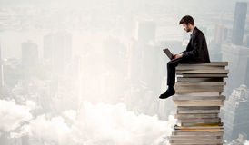 Student in city sitting on stack of books Stock Photo