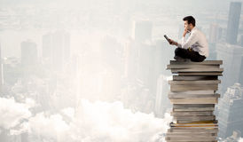 Student in city sitting on stack of books Stock Photography