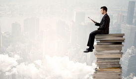 Student in city sitting on stack of books Royalty Free Stock Photo