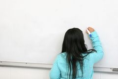 Student in class. One young student writing on a blank whiteboard Stock Photo