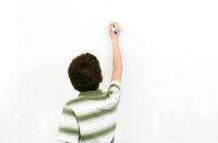 Student in class. One young boy student writing on a blank whiteboard Stock Photography