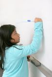 Student in class. One young student writing on a blank whiteboard Royalty Free Stock Photo