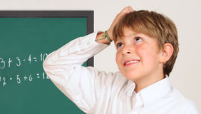 Student in a classroom. Student scratching his head in a classroom Royalty Free Stock Images