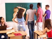 Student in classroom near blackboard. Royalty Free Stock Image