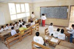 Student in classroom writing Arabic on blackboard Stock Photos