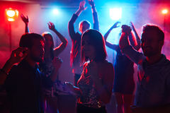 Student club party. Young pretty girl in shining top dancing with male friends at student disco party and enjoying music with her eyes closed Stock Photography